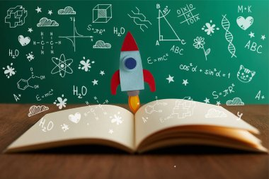 open book with colorful rocket on wooden table with math icons