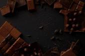 pohled shora na různé kousky lahodné čokolády na černém pozadí