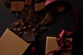Photo top view of gourmet chocolate pieces with nuts and gift box on black