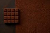 Fotografie pohled shora lahodné hnědé kakaového prášku a chutné čokolády na černém pozadí