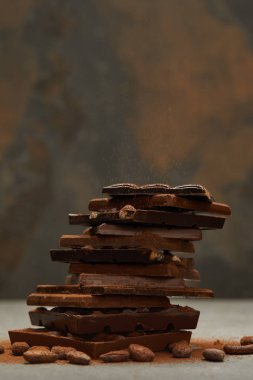 close-up view of stacked delicious assorted chocolate pieces and nuts on grey