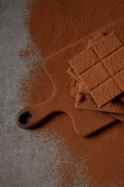 top view of sweet tasty chocolate pieces with cocoa powder on chopping board on grey