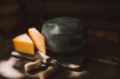 zwei Arten von Käse und Besteck auf rustikalen Holztisch