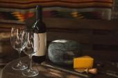 Nahaufnahme von Käse und Wein am rustikalen Holztisch