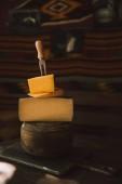 Fotografie Detailní záběr naskládány různé druhy sýr plátky s vidličkou na rustikální dřevěný stůl
