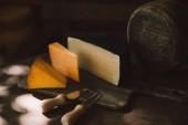 Fotografie různé druhy lahodných sýrů s příbory sýr na rustikální dřevěný stůl