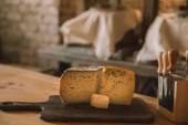 Fotografia primo piano sparato di fette di formaggio sul tagliere con coltelli vari stand