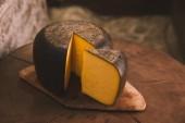 Fotografie lahodný plátkový sýr na rustikální dřevěné prkénko