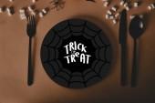 felülnézet fekete lemez pókháló fogás vagy élvezet betűkkel, Villa és kés marshmallows asztalon, halloween koncepció