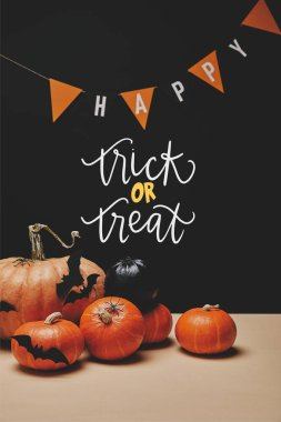 pumpkins, paper bats and paper garland with word happy and with