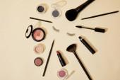 Draufsicht auf verschiedene Kosmetika, die auf beiger Oberfläche um falsche Wimpern herum liegen