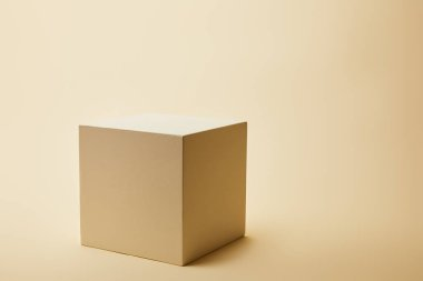 Close-up shot of single cube on beige surface stock vector