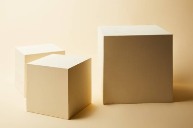 still life of cubes in different sizes on beige surface