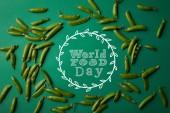 pohled shora na kulatý rám vyroben z hrachové lusky na zeleném povrchu s nápisem Světový den potravin