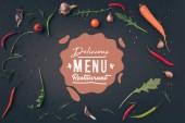 pohled shora rukoly, mrkví a chilli papričkami na šedém povrchu s nápisem lahodné menu restaurace