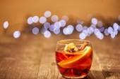 Nahaufnahme von Glühweingetränk mit Orangenstücken und Anissternen auf Holzoberfläche mit Bokeh-Lichtern im Hintergrund