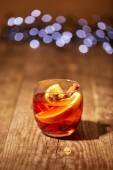 Fotografie close up view of mulled wine drink with orange pieces and anise stars on wooden surface with bokeh lights on background