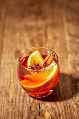 close up view of hot mulled wine drink with orange pieces and anise stars on wooden tabletop