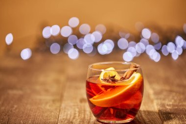 close up view of mulled wine drink with orange pieces and anise stars on wooden surface with bokeh lights on background