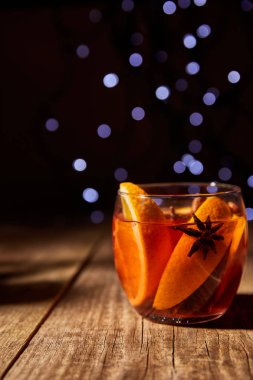 close up view of hot mulled wine drink with orange pieces and anise stars on wooden surface with bokeh lights on background