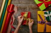 Fotografia ritagliata colpo di nastro che lega donna il presente di Natale spostato su superficie di legno con altri doni
