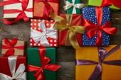 Fotografia lay flat con i regali di Natale avvolto in documenti di disposizione diverso con i nastri su superficie di legno