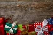 Photo flat lay with presents wrapped in different wrapping papers with ribbons on wooden background