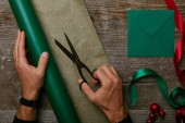 Fotografie partial view of man with scissors, wrapping paper for gift wrapping and envelope on wooden tabletop