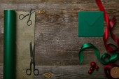 flat lay with blank envelope, scissors, green and red ribbons and wrapping paper on wooden surface, christmas background