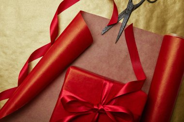 top view of scissors and christmas present with ribbon on red and golden wrapping papers background