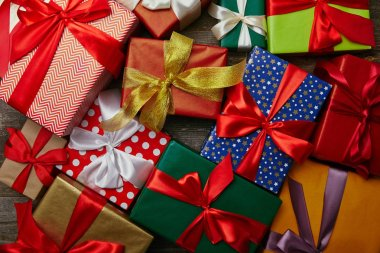 flat lay with christmas presents wrapped in different wrapping papers with ribbons on wooden surface