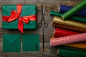 flat lay with christmas gift with red ribbon, wrapping papers, scissors and envelopes for greeting card on wooden surface