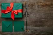 Fotografie plochý ležela s zabalený vánoční dárek s červenou stužkou, nůžky a obálky pro přání na dřevěný povrch