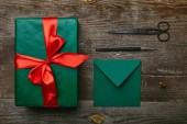 lapos feküdt becsomagolt karácsonyi ajándék piros szalag, olló és boríték üdvözlőlap fa felületre