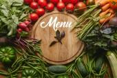 Výběr čerstvé zeleniny a bylinek v prkénku s nápisem menu