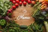 Rám zdravé zelené a červené zeleniny na dřevěný stůl s nápisem zdravé menu