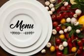 pohled shora kruhové bílé desky s nápisy menu a čerstvá zelenina na dřevěný povrch