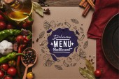 Fotografie top view of card with delicious menu restaurant lettering, spices and vegetables on wooden surface