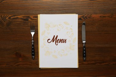 Top view of Menu with fork and knife on wooden table stock vector