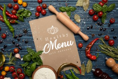 top view of fresh raw vegetables, spices, rolling pin and card with