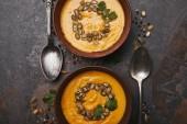 Fotografia vista superiore delle ciotole con gustosa zuppa di zucca, cucchiai e spezie su superficie scura