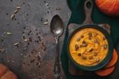 Fotografie pohled shora chutné zdravé Dýňová polévka v misku a lžíci na tmavý podklad