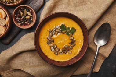 top view of bowl with delicious pumpkin soup and spoon on sackcloth