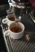 close-up view of coffee maker and two cups with espresso