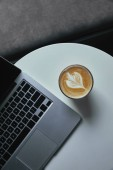 Fotografie top view of cup of cappuccino and laptop on table in cafe