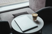 high angle view of laptop and cup of cappuccino on table in coffee shop