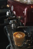 close-up view of coffee machine and glass cup with cappuccino