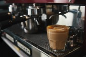 close-up view of glass cup with cappuccino and coffee maker