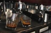 close-up of coffee maker preparing espresso in two cups