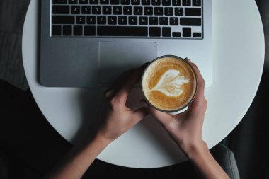 cropped shot of person holding cup with cappuccino and using laptop